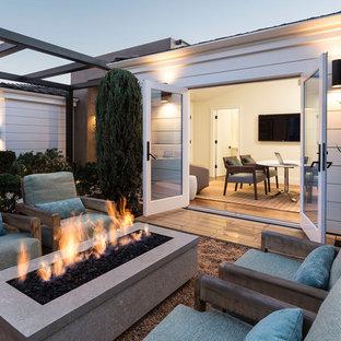 Esempio di un patio o portico minimal dietro casa con un focolare, ghiaia e nessuna copertura