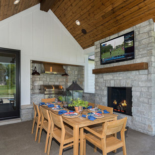 Medium sized rural back patio in Indianapolis with a fire feature, concrete paving and an awning.