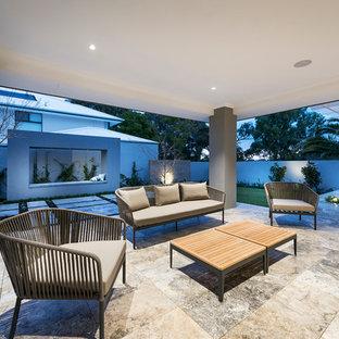 Immagine di un grande patio o portico vittoriano dietro casa con piastrelle e un tetto a sbalzo