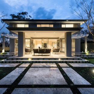 Foto di un grande patio o portico vittoriano dietro casa con piastrelle e un tetto a sbalzo