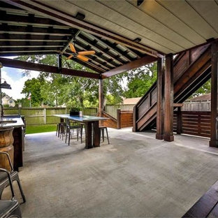 Large urban backyard concrete patio kitchen photo in Houston with a roof extension