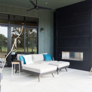 Foto di un piccolo patio o portico eclettico dietro casa con un caminetto, lastre di cemento e un tetto a sbalzo