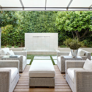 Design ideas for a medium sized contemporary back patio in Phoenix with a water feature, decking and an awning.