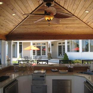 Inspiration for a large craftsman backyard concrete patio kitchen remodel in Boston with a gazebo
