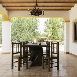 Imagen de patio mediterráneo con suelo de baldosas y pérgola
