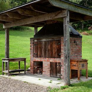 Idee per un patio o portico country dietro casa con un focolare
