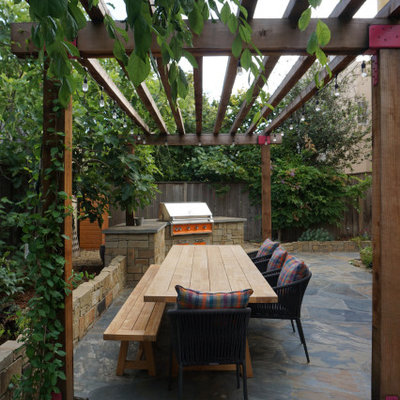 Mid-sized transitional backyard stone patio photo in San Francisco with a pergola