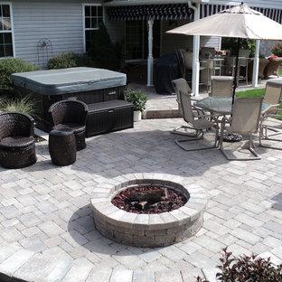 Foto di un patio o portico chic di medie dimensioni e dietro casa con un focolare, pavimentazioni in cemento e nessuna copertura