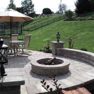 Mid-sized elegant backyard concrete paver patio photo in Other with a fire pit and no cover