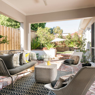 This is an example of a mid-sized transitional backyard patio in Perth with a container garden, brick pavers and a roof extension.
