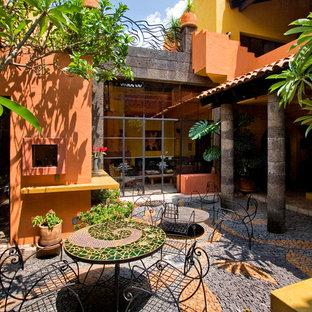Esempio di un patio o portico boho chic in cortile e di medie dimensioni con un giardino in vaso e pavimentazioni in pietra naturale