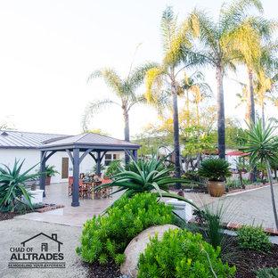 Esempio di un ampio patio o portico eclettico davanti casa con un giardino in vaso, piastrelle e un gazebo o capanno