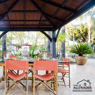 Immagine di un ampio patio o portico boho chic dietro casa con piastrelle e un gazebo o capanno