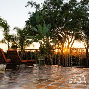 Idee per un ampio patio o portico eclettico dietro casa con piastrelle e nessuna copertura