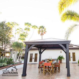 Immagine di un ampio patio o portico bohémian davanti casa con piastrelle e un gazebo o capanno
