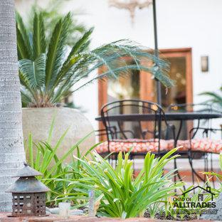 Idee per un ampio patio o portico eclettico dietro casa con piastrelle