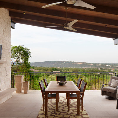 Inspiration for a mid-sized contemporary side yard tile patio remodel in Austin with a fire pit and a roof extension