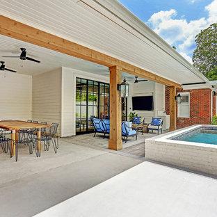 Ispirazione per un patio o portico chic dietro casa con cemento stampato e un tetto a sbalzo