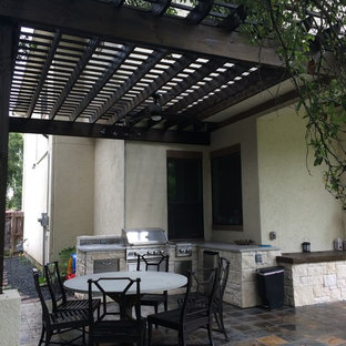 Example of a trendy backyard stone patio kitchen design in Houston with a pergola