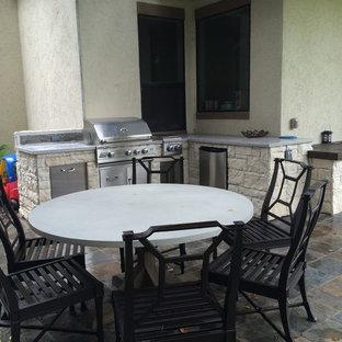 Trendy side yard stone patio kitchen photo in Houston with a pergola
