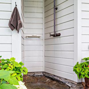 Foto di un patio o portico country dietro casa con pavimentazioni in pietra naturale e un tetto a sbalzo