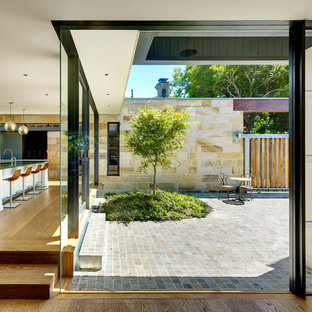 This is an example of a contemporary courtyard patio in Sydney with tile and no cover.