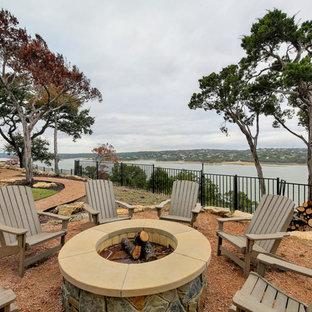 Idee per un grande patio o portico costiero dietro casa con un focolare, graniglia di granito e nessuna copertura