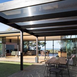 Esempio di un grande patio o portico design nel cortile laterale con lastre di cemento e un tetto a sbalzo