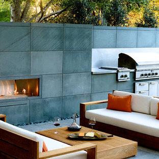 Immagine di un patio o portico contemporaneo di medie dimensioni e dietro casa con un focolare e lastre di cemento