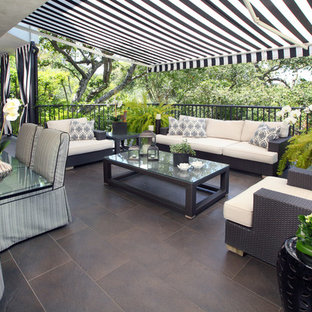 Inspiration for a medium sized contemporary back patio in Los Angeles with tiled flooring and an awning.