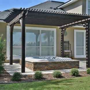Inspiration for a mid-sized transitional backyard stone patio remodel in Jacksonville with a pergola