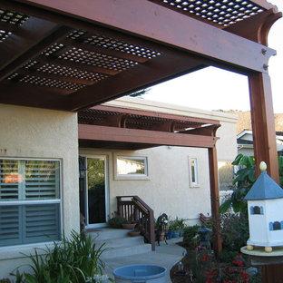 Idee per un grande patio o portico costiero dietro casa con cemento stampato e una pergola