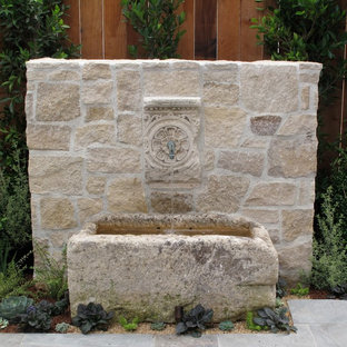 Example of a mid-sized tuscan courtyard stone patio fountain design in New York with no cover