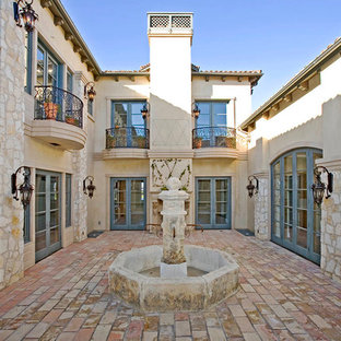 Example of a mid-sized tuscan courtyard stone patio fountain design in New York