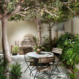 Patio fountain - mid-sized mediterranean courtyard stone patio fountain idea in New York