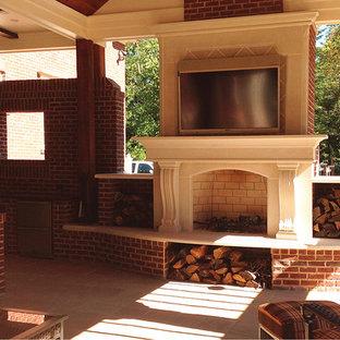 Immagine di un grande patio o portico chic dietro casa con pavimentazioni in pietra naturale, un tetto a sbalzo e un focolare