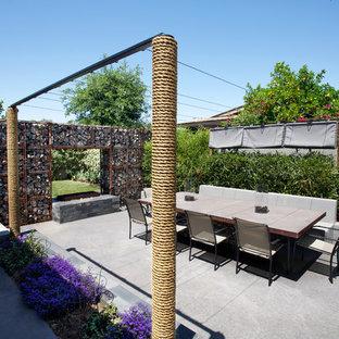 Idee per un patio o portico industriale di medie dimensioni e dietro casa con un focolare, nessuna copertura e lastre di cemento