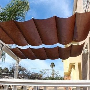 Mid-sized minimalist backyard patio photo in Orange County with an awning