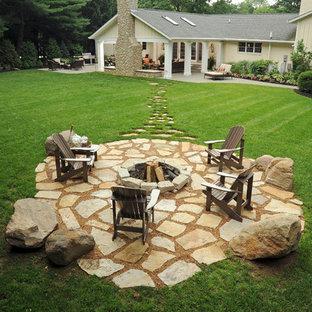 Cette photo montre une grande terrasse et balcon arrière chic avec des pavés en pierre naturelle et un foyer extérieur.