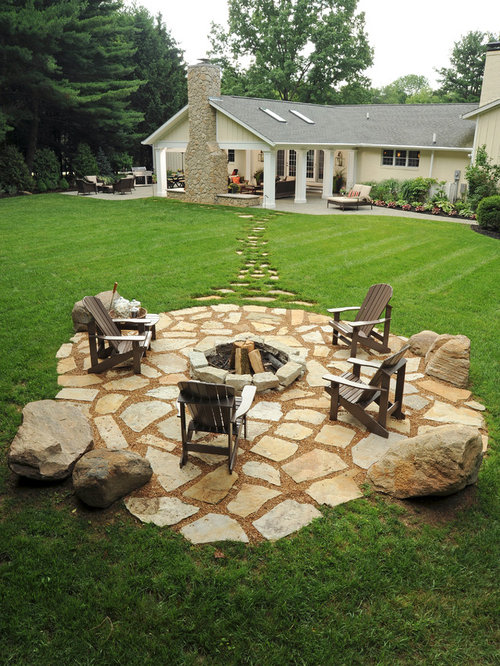 Inspiration for a large traditional full sun backyard stone landscaping in  Columbus with a fire pit