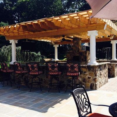 Large elegant backyard stone patio kitchen photo in New York with a pergola