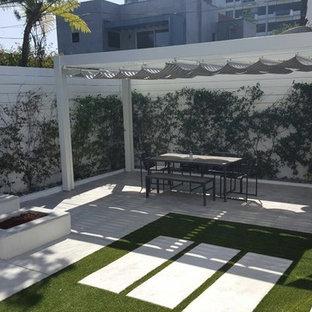 Esempio di un piccolo patio o portico minimalista dietro casa con un focolare, lastre di cemento e un gazebo o capanno
