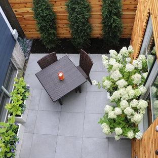 Esempio di un piccolo patio o portico contemporaneo dietro casa con piastrelle e nessuna copertura