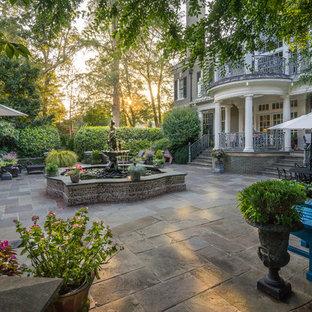 Immagine di un grande patio o portico tradizionale dietro casa con fontane, pavimentazioni in pietra naturale e un tetto a sbalzo