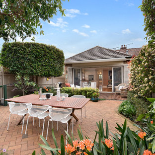 This is an example of a transitional courtyard patio in Sydney with brick pavers.