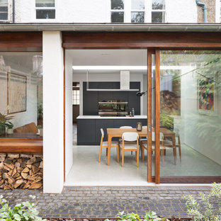 This is an example of a contemporary back patio in London with concrete paving and no cover.