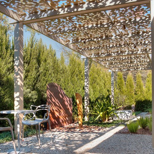 Patio - small contemporary backyard gravel patio idea in Houston with a pergola