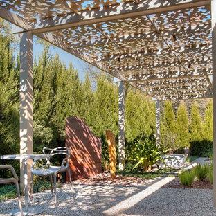 Idee per un piccolo patio o portico contemporaneo dietro casa con ghiaia e una pergola