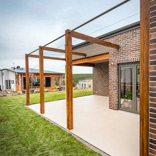 Immagine di un patio o portico minimalista di medie dimensioni e dietro casa con piastrelle e nessuna copertura