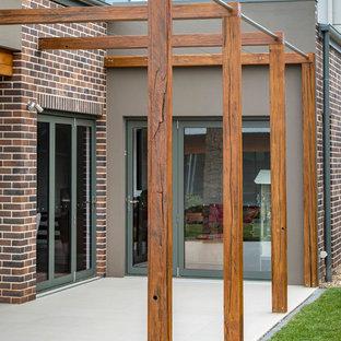 Foto di un patio o portico moderno di medie dimensioni e dietro casa con piastrelle e nessuna copertura